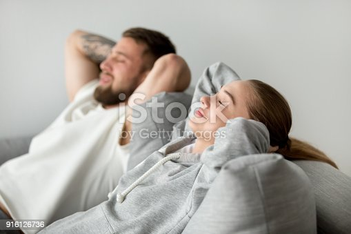 1143763067istockphoto Relaxed young couple relaxing on comfortable sofa together at ho 916126736