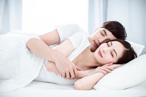 relaxed Young  couple sleep together in bed
