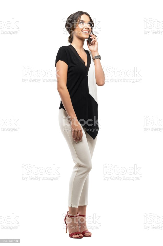 Relaxed young elegant business woman talking on the phone smiling and looking up. stock photo
