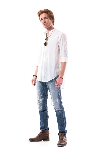 931173966 istock photo Relaxed young fashionable red head man standing and looking at camera with arms down 1255243815