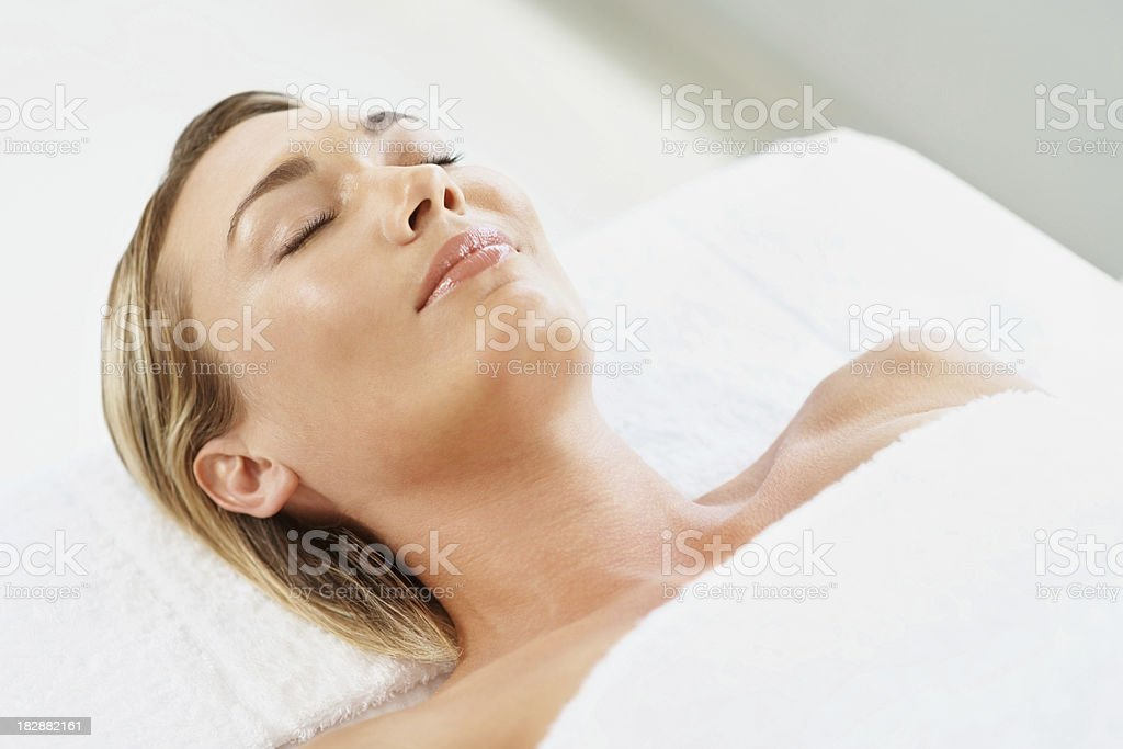 Relaxed young female with eyes closed lying at spa - Royalty-free 30-34 Years Stock Photo