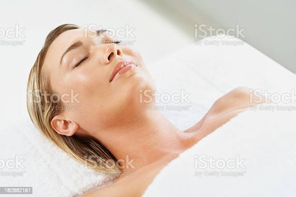 Relaxed Young Female With Eyes Closed Lying At Spa Stock Photo - Download Image Now