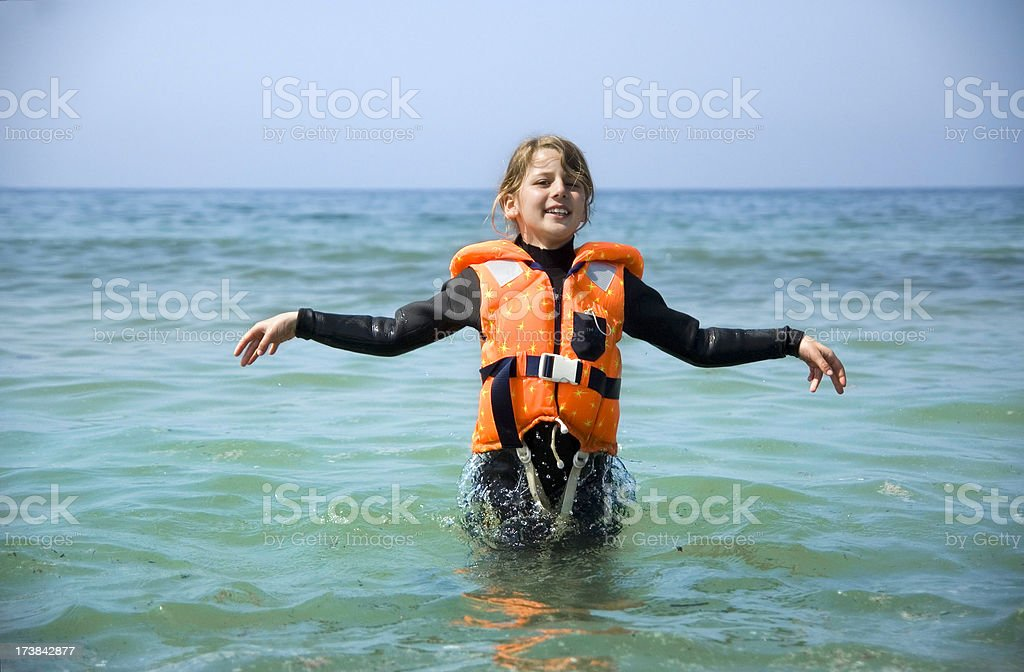 Relaxed young girl with life jacket standing in the water royalty-free stock photo