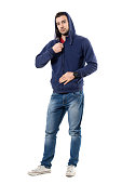Relaxed young guy fastening zipper on hoodie getting dressed