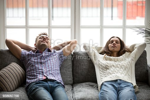 1143763067istockphoto Relaxed young man and woman enjoying relaxation on comfortable couch 938682756
