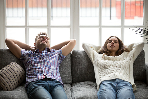 973962076 istock photo Relaxed young man and woman enjoying relaxation on comfortable couch 938682756