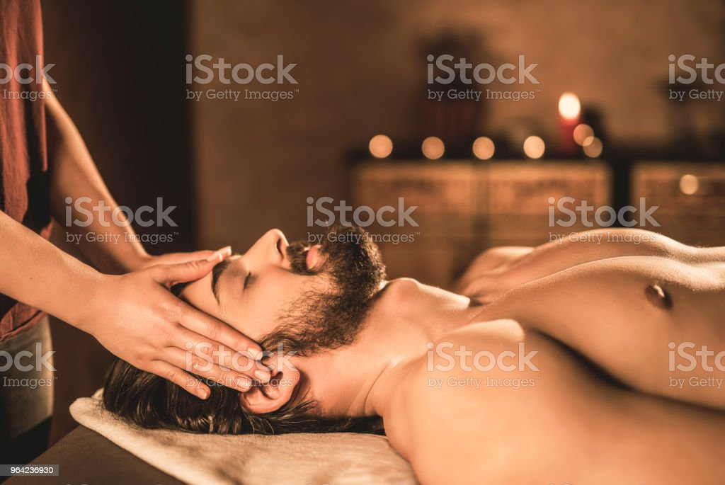 Relaxed young man enjoying a head massage side view.