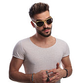 relaxed young man in retro sunglasses standing on white background