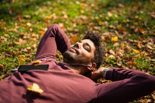 homem novo relaxed que coloca na terra e que escuta a música no dia do outono. - meditation - fotografias e filmes do acervo
