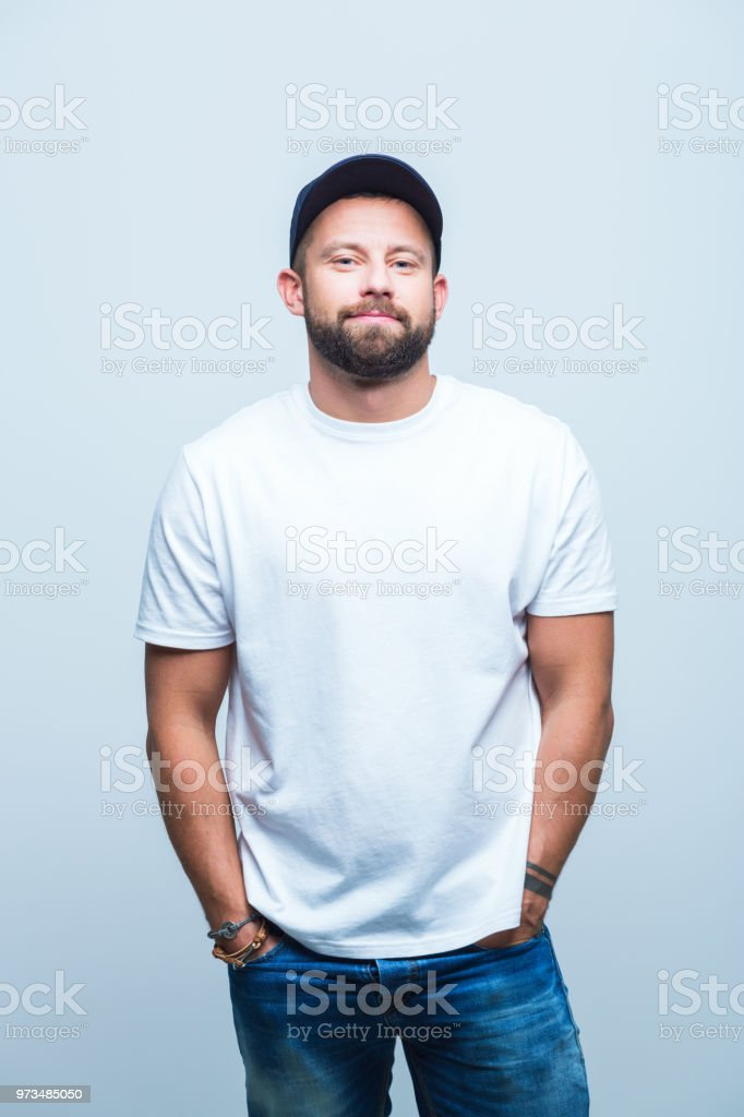 Relaxed young man Portrait of young man standing relaxed. Male model with hands in pocket on white background Adult Stock Photo