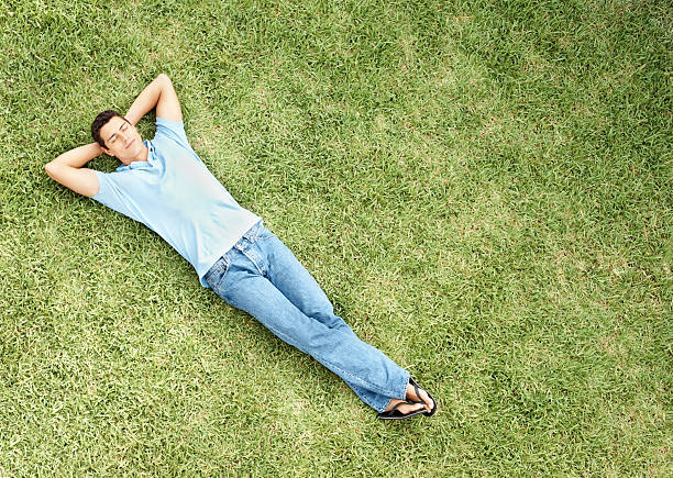relaxed young man sleeping on grass - reclining stock photos and pictures
