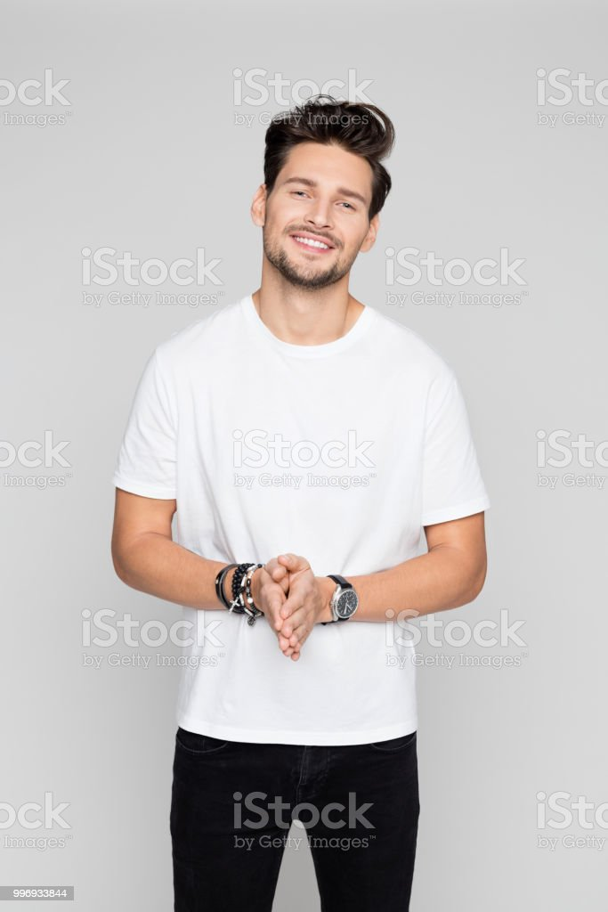 Relaxed young man standing confidently Portrait of relaxed young man standing confidently on grey background 25-29 Years Stock Photo