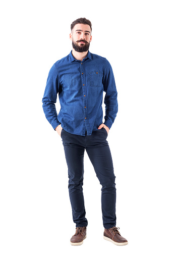 931173966 istock photo Relaxed young man wearing blue denim shirt with hands in pockets looking at camera 931173966