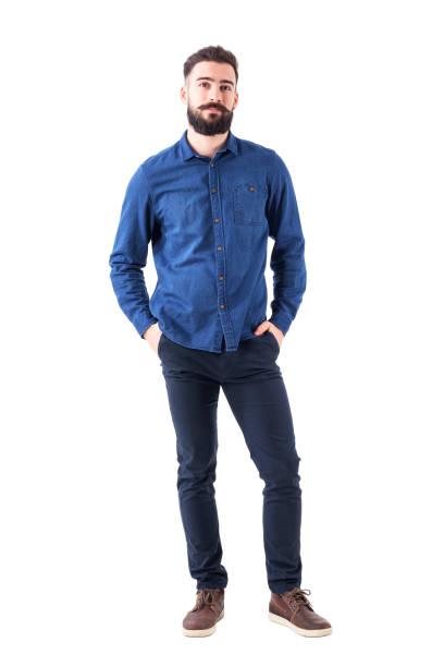 relaxed young man wearing blue denim shirt with hands in pockets looking at camera - casual clothing stock photos and pictures