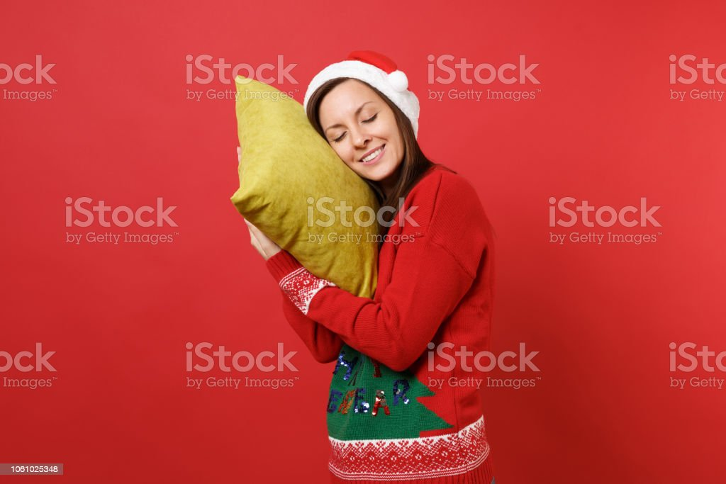Relaxed young Santa girl in Christmas hat holding pillow keeping eyes...