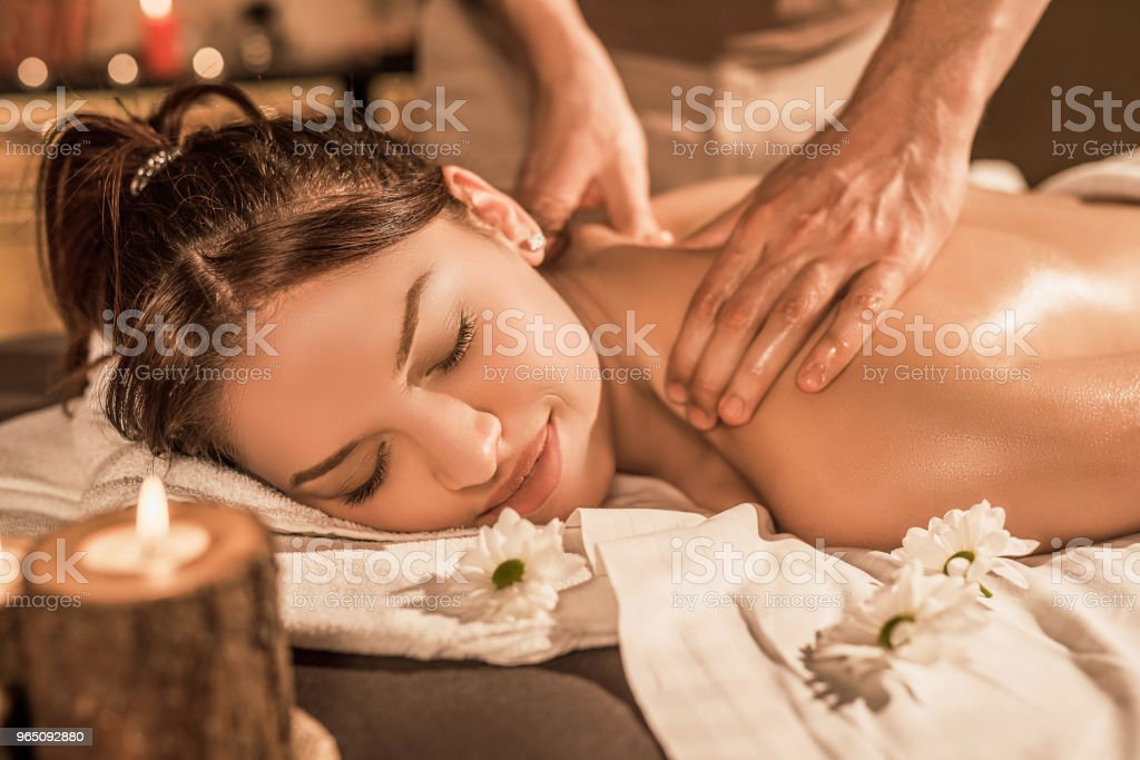 Relaxed young woman enjoying a back massage. zbiór zdjęć royalty-free