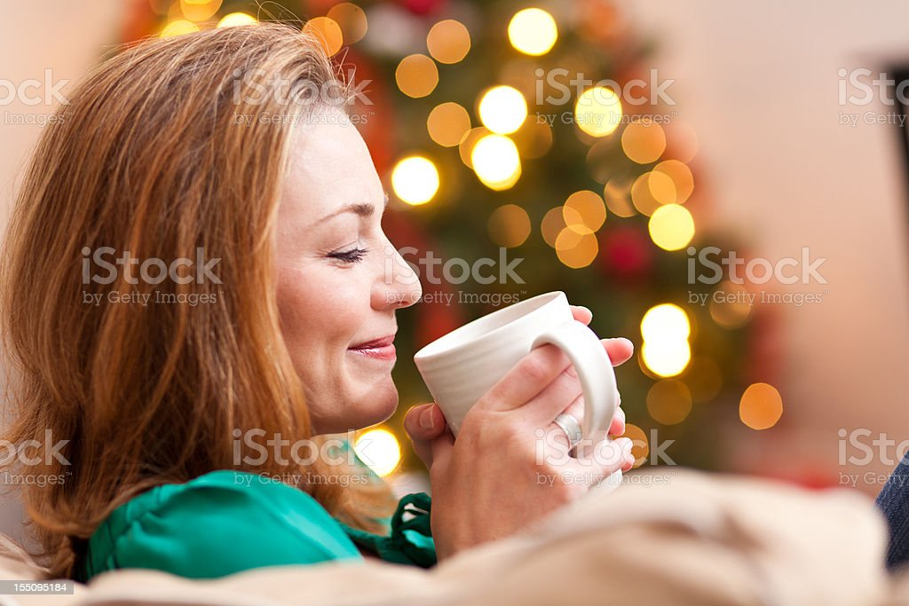 Relaxed young woman enjoying hot drink at Christmas time royalty-free stock photo