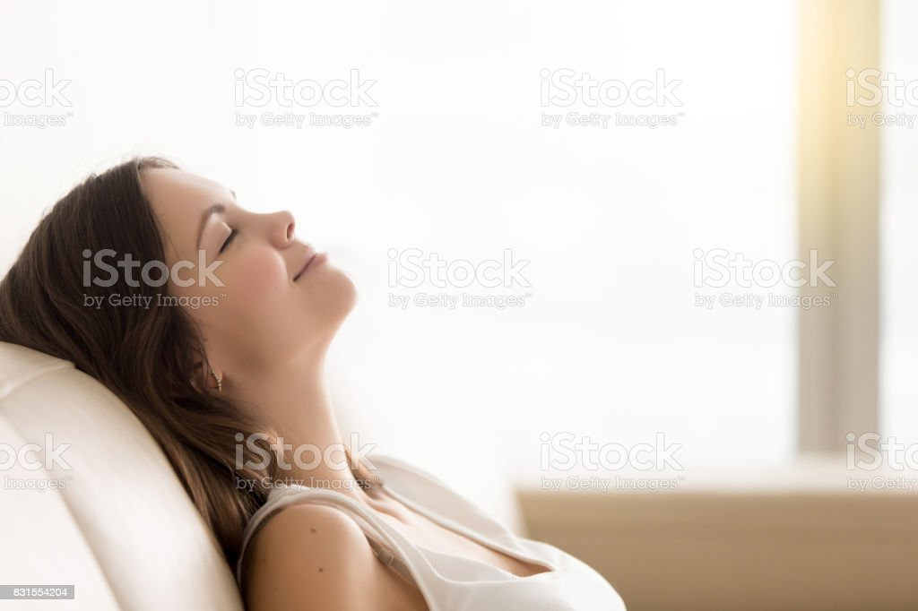 Relaxed young woman enjoying rest on comfortable sofa, copy space stock photo