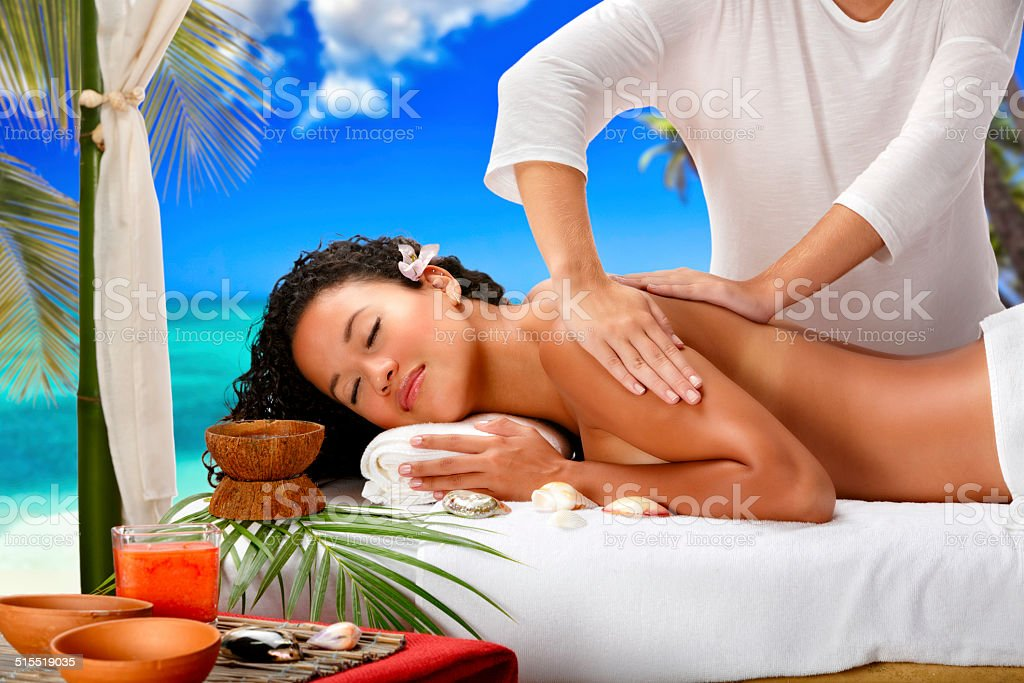 Relaxed young woman getting massage therapy in Spa beach resort stock photo