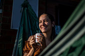 istock Relaxed young woman having a cup of coffee 1295976918