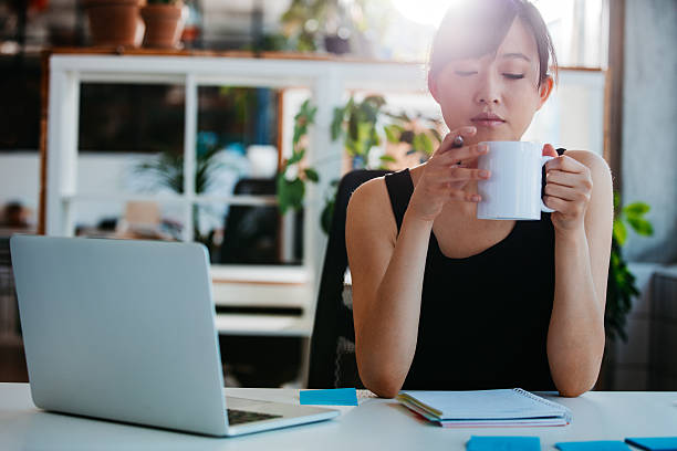 Relaxed young woman having coffee at her desk stock photo