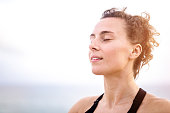 Relaxed young woman meditating outdoors by the sea head close up.