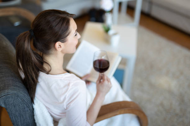 Relaxed young woman reading a book stock photo