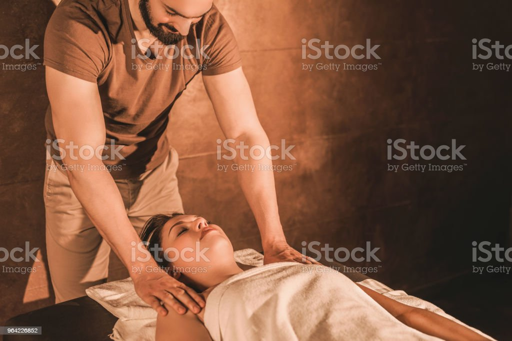 Relaxed young woman receiving a shoulder massage from male massage...