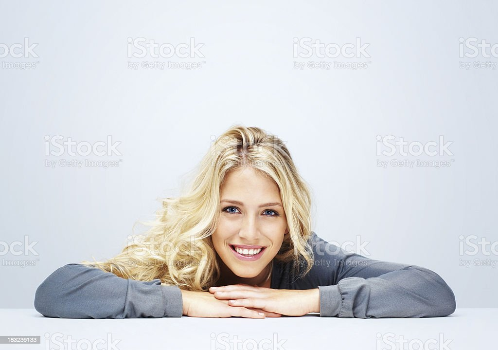 Relaxed young woman smiling against white background royalty-free stock photo