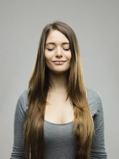 Relaxed young woman studio portrait stock photo