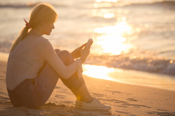Relaxed young woman using her mobile phone to text at the beach during sunset. Peaceful female person text messaging on her smartphone. She is sitting alone outdoors on the sand near the water with a beautiful reflection of the sun. long distance relationship stock pictures, royalty-free photos & images