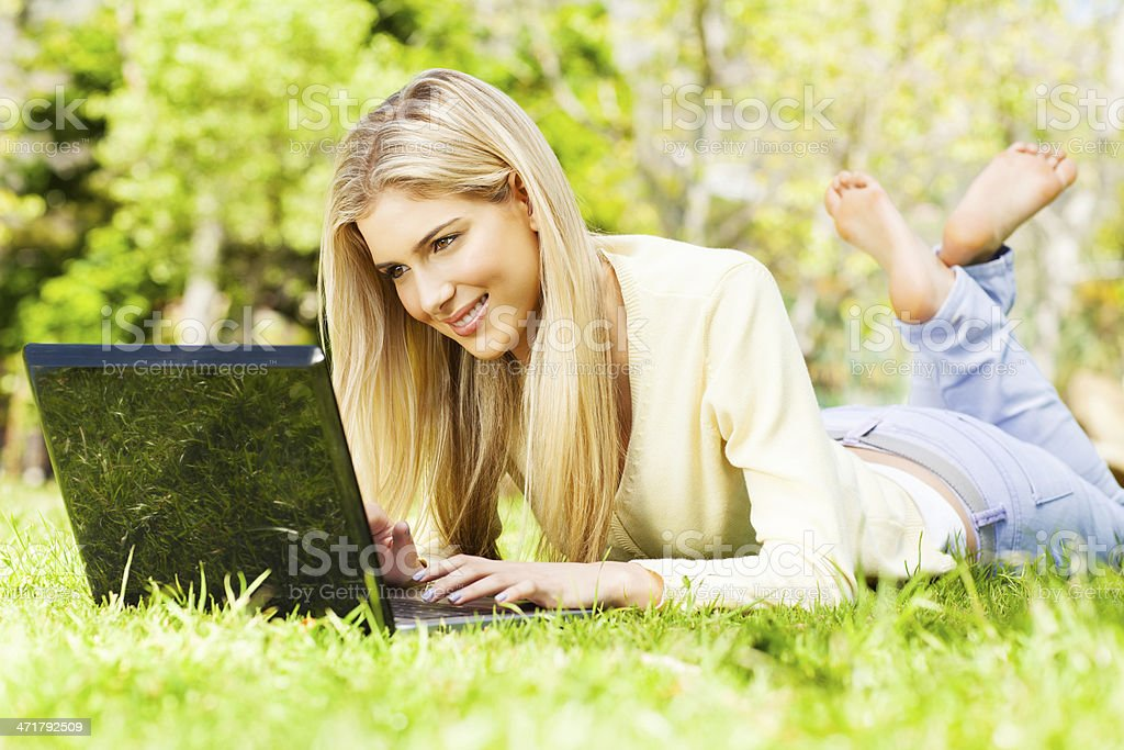 Relaxed Young Woman Using Laptop In Park. stock photo
