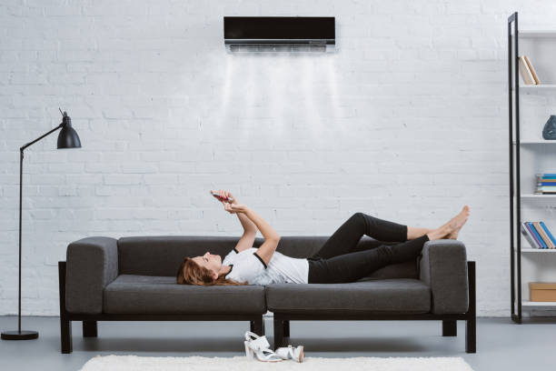 avslappnad ung kvinna med smartphone på soffan under luftkonditioneringen hängande på väggen - kvinna ventilationssystem bildbanksfoton och bilder