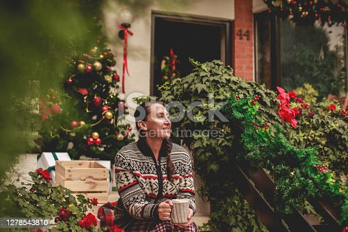 Candid shot of relaxed woman sitting on the staircase of the entrance of her house and enjoying after decorating for Christmas season.