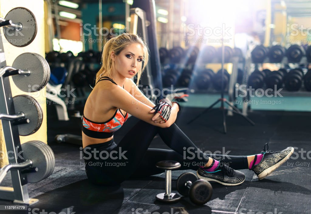 Relaxing After Training Beautiful Young Woman Sitting At Gym And Having A Brake After Exercize Young Female At Gym Taking A Break From Workout Sports Fitness Model Healthy Lifestyle Concept Stock Photo