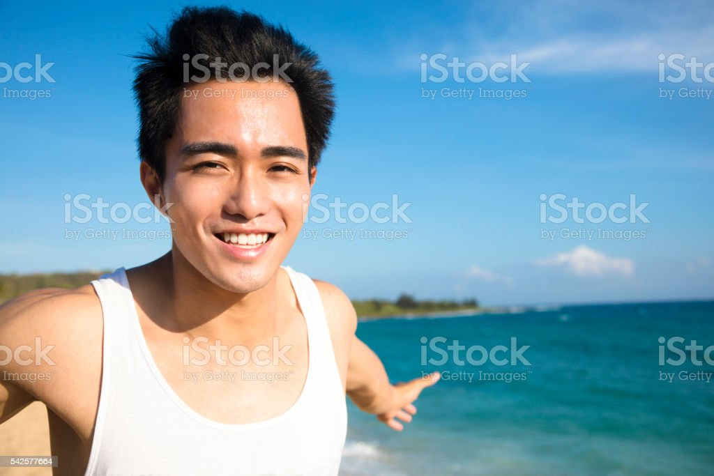 relaxing and smiling young man on the beach stock photo