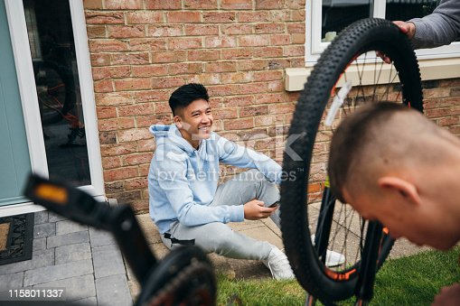 A teenage boy sits, relaxing on his smart phone, while his friends are fixing a bicycle. He is looking at his friends, smiling and laughing.