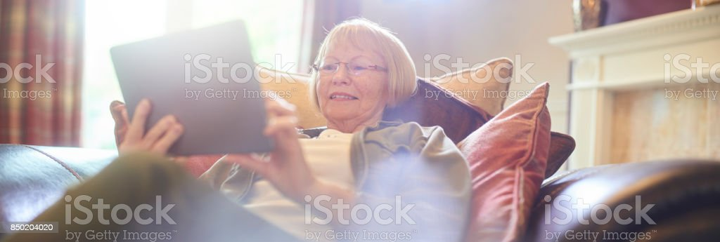 relaxing at home on her digital tablet stock photo