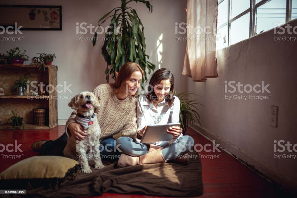 Relaxing at home Horizontal photo of mother and daughter using digital tablet at their cosy living room. 12-13 Years Stock Photo