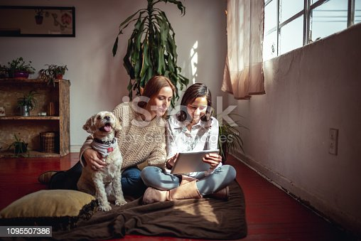 Horizontal photo of mother and daughter using digital tablet at their cosy living room.