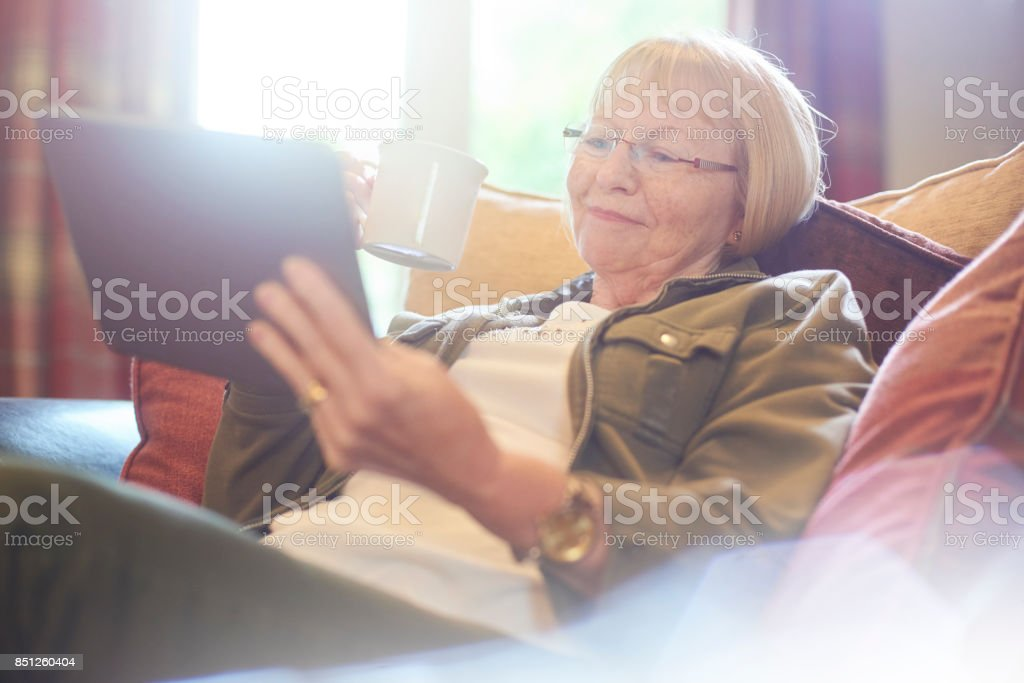 relaxing at home with a brew and her digital tablet stock photo
