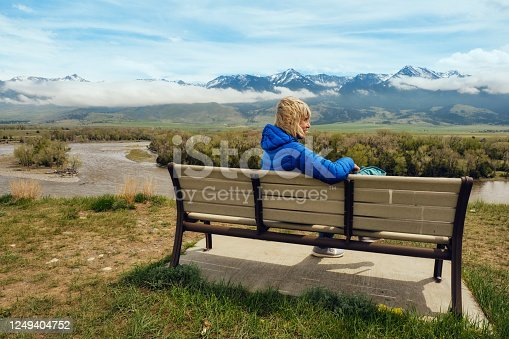 Senior woman relaxing on a bench at a popular viewpoint above the Yellowstone River at Paradise Valley, Montana, USA.