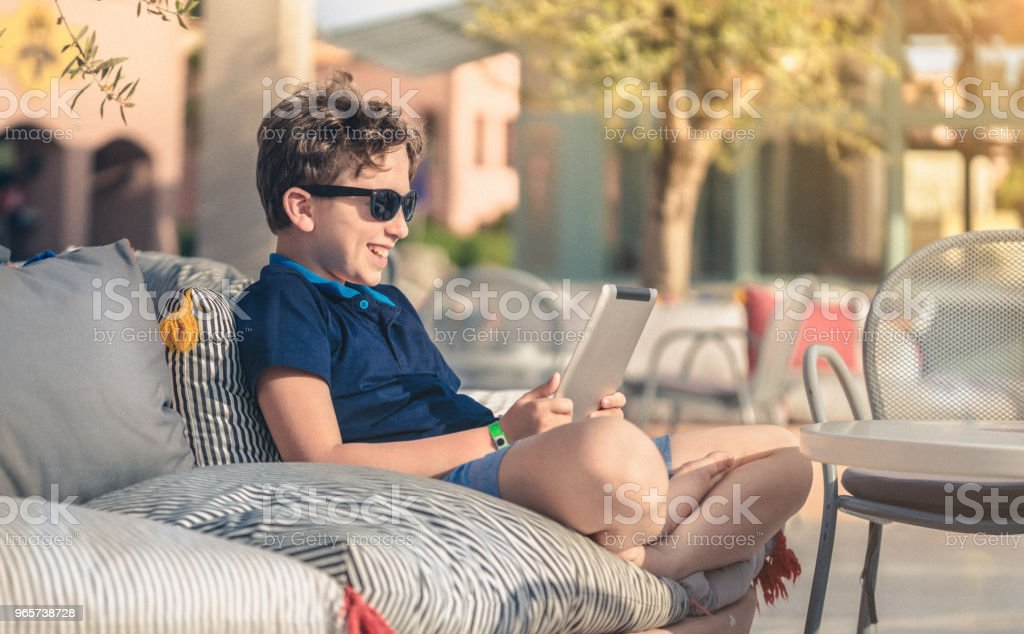 Relaxing at sunset with digital tablet on vacation - Royalty-free Beach Stock Photo