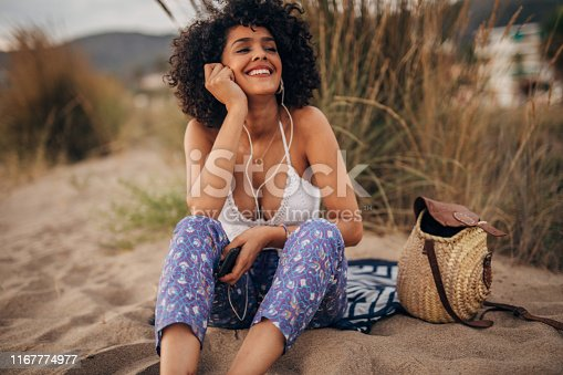 Woman listening music and relaxing at the beach