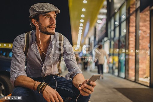 Young man listening to music on a mobile phone while sitting on the bench at the shooping center