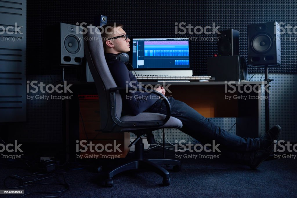 Tired sound engineer relaxing at workplace