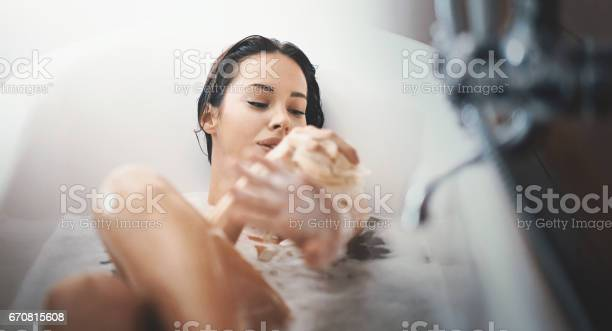 Closeup of attractive mid 20's woman taking a long bath in a bathtub. She's slowly scrubbing off with a bath sponge and not planning to get out some time soon.