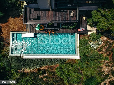Aerial view of a three friends relaxing by the pool