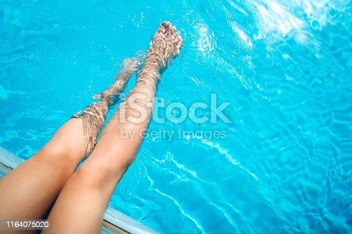 694409862 istock photo Relaxing by the swimming pool 1164075020