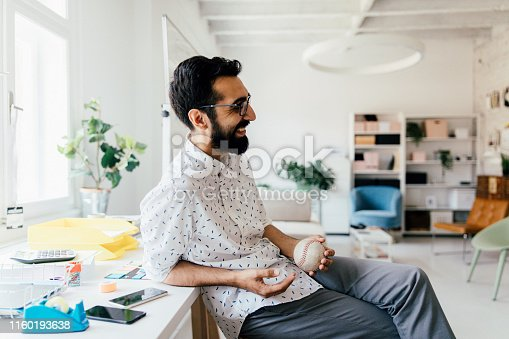 Photo of a young man, taking a rest and relaxing during work hours in his office
